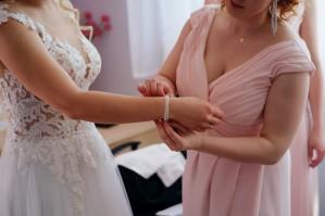 Przygotowania świadkowa nakłada biżuterię ślubną
