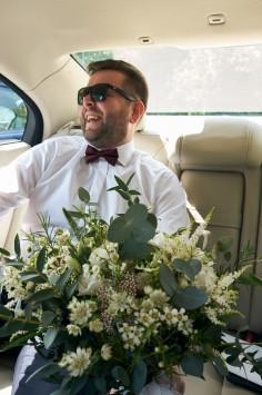 Przygotowania Pan Młody w samochodzie z bukietem