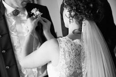Przygotowania Pani Młoda przypina przypinkę z kwiatkiem