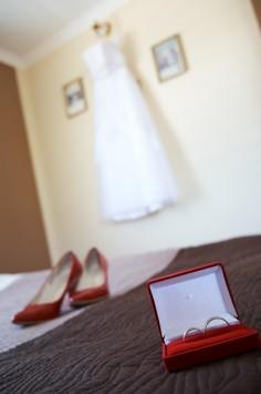 Przygotowania Pani Młodej Suknia ślubna czerwone buty ślubne i pudełko na obrączki