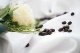 Wesele detal stołu biała róża z ziarnami kawy
